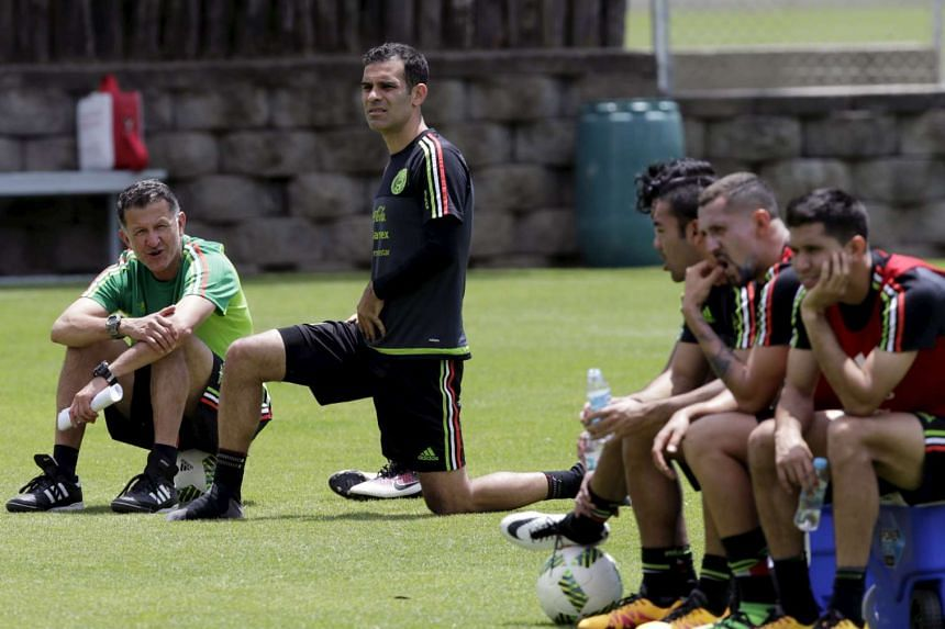 Mexico's national soccer team head coach Juan Carlos Osorio (left) talks with his player Rafael Marquez (2nd left) next to other teammates during a training session in preparation for their qualifying match against Canada.
