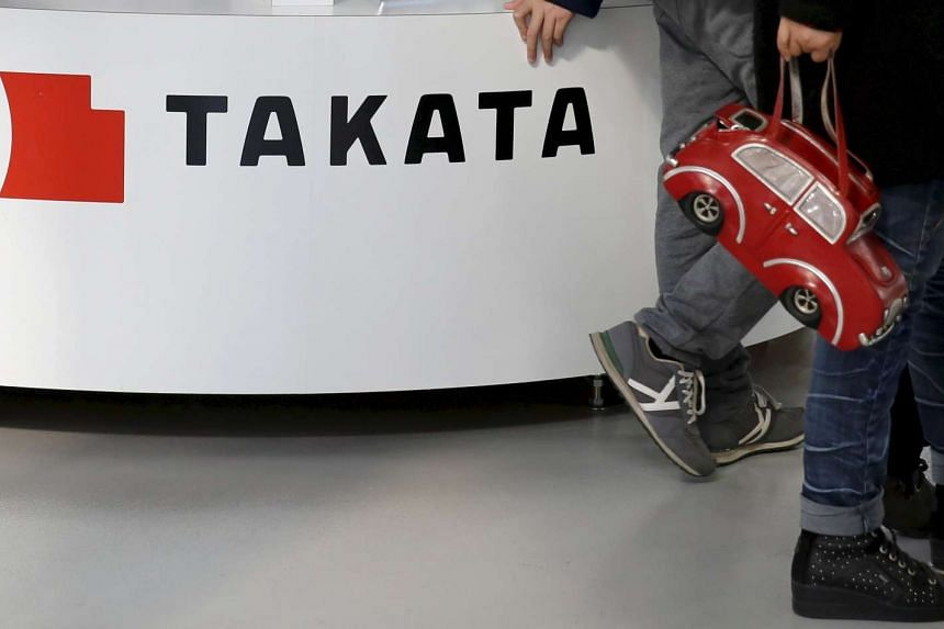 Visitors walk past a logo of Takata Corp at a showroom for vehicles in Tokyo.