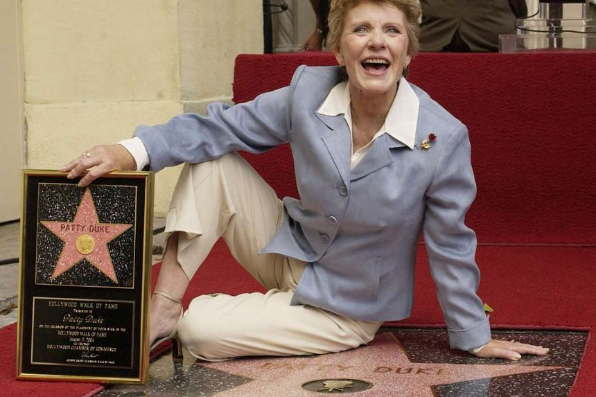 Award-winning actress Patty Duke poses for photographers following an unveiling ceremony honoring her star on the Hollywood Walk of Fame, in Los Angeles, California, in this file photo taken on Aug 17, 2004.