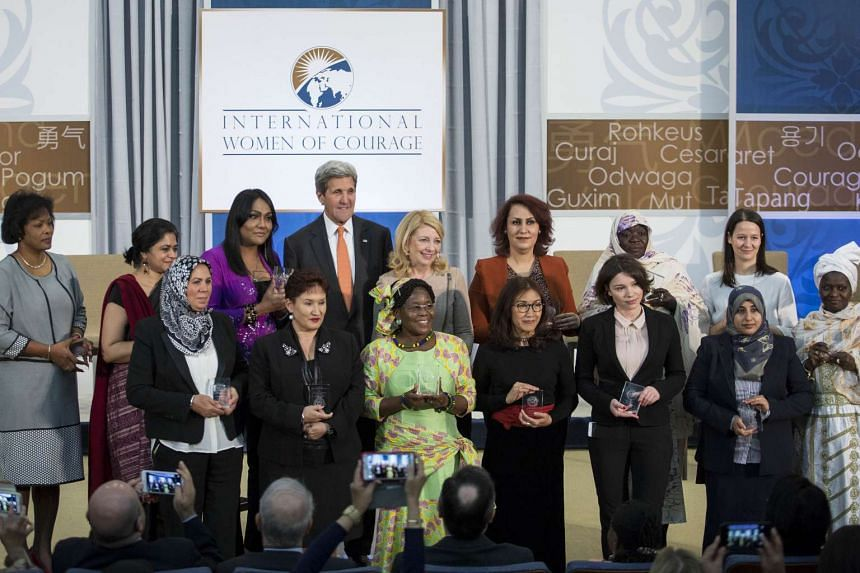 Us Secretary of State John Kerry poses with honorees for a group photo during a ceremony to present the 2016 Secretary of State's International Women of Courage Award at the State Department on March 29, 2016 in Washington, DC.
