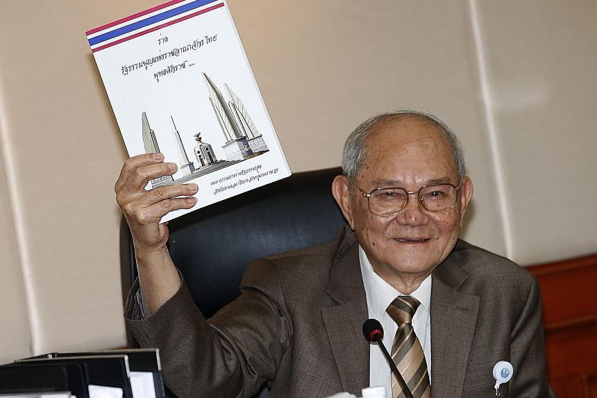 Constitution drafting committee chairman Meechai Ruchupan with a copy of the draft Constitution yesterday.