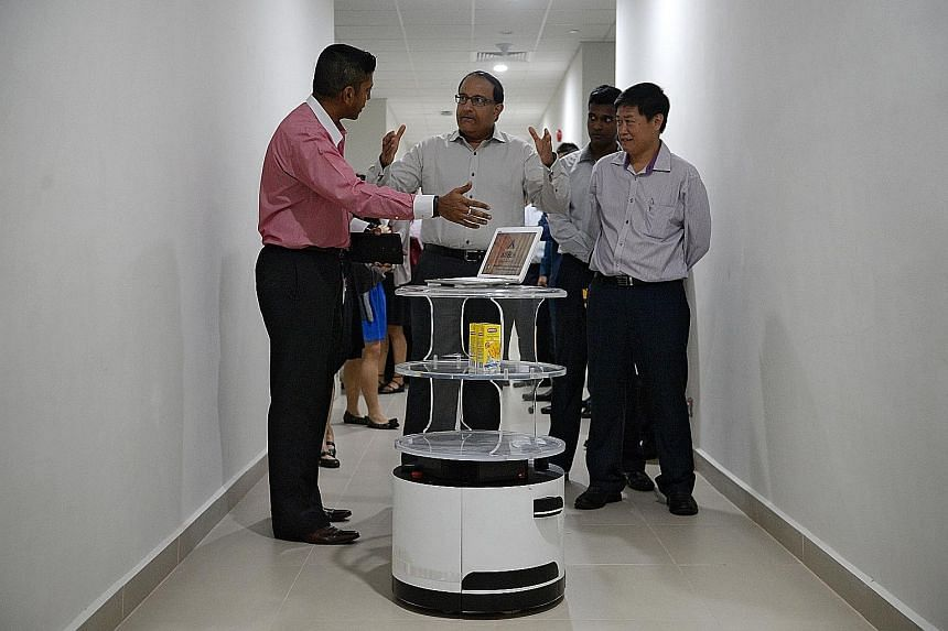 Mr Iswaran (centre) with Aitech Robotics and Automation industry robot engineer Sean Efrem Sabastian (far left) and business development manager Eric Lee at a demonstration of Aitech's food and beverage service robot's capabilities yesterday.