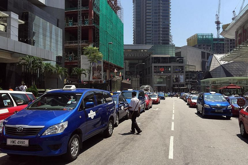 Taxis lining the street outside Pavilion shopping centre in Jalan Bukit Bintang in Kuala Lumpur yesterday, blocking the main road into the area. The police moved in to arrest five protesters and towed away the cabs that had not budged after a warning