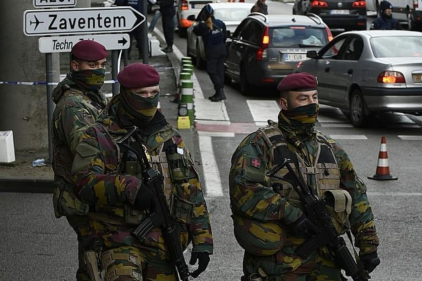 Belgian soldiers and police securing routes to Brussels airport yesterday. The airport's chief executive Arnaud Feist said it could take months for it to be fully operational again.