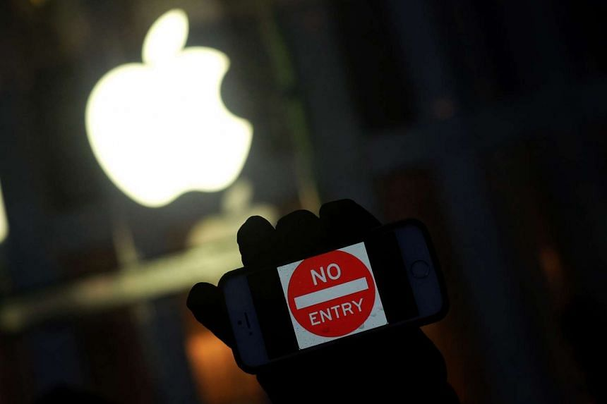 "An anti-government protester holding his iPhone with a sign ""No Entry"" during a demonstration on March 25, 2016."