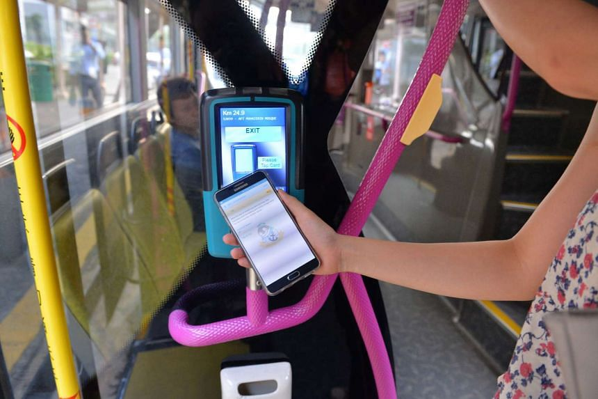 Photograph illustration showing a compatible smartphone with Near Field Communication being used on a bus.