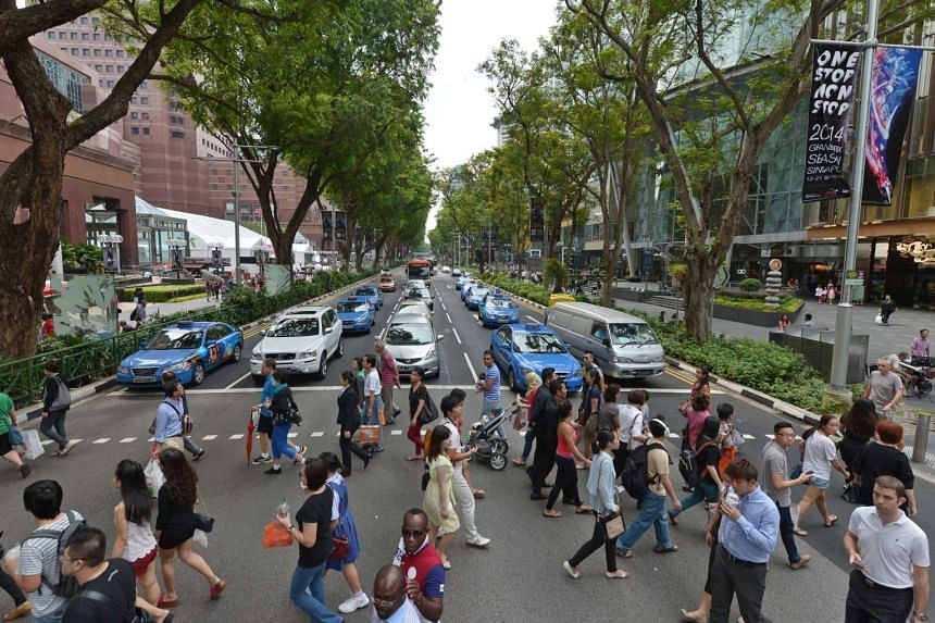Shoppers crossing at the traffic crossing between Ngee Ann City and Paragon at Orchard Road.