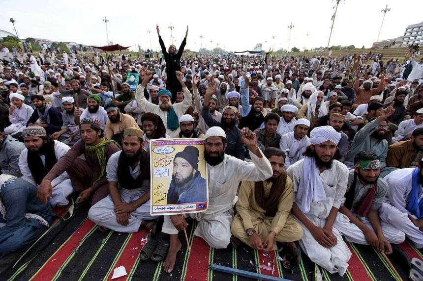 A man holding a picture of Mumtaz Qadri during a sit-in protest against his execution, in Islamabad, on March 29.