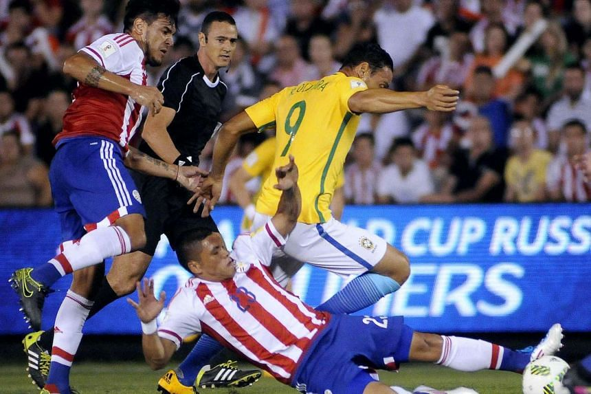 Richard Ortiz (on the ground) and Gustavo Gomez (left) of Paraguay in action against Ricardo Oliveira (centre) of Brazil during their Fifa World Cup 2018 Qualification football match.