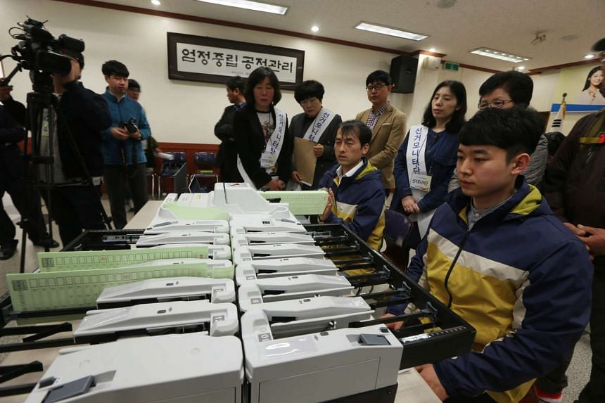 Regional election commission workers perform a public rehearsal for vote counting in South Korea on March 8, 2016.