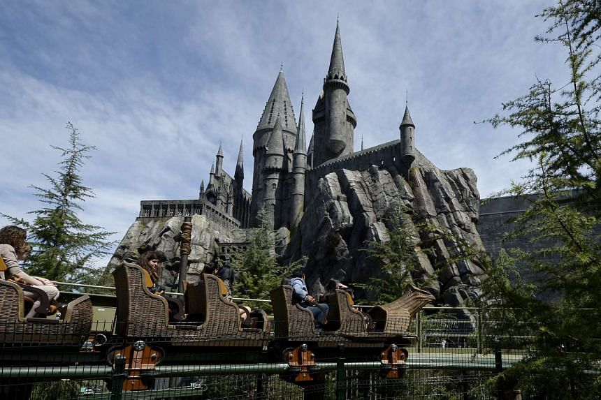 Parkgoers on a roller coaster outside the Hogwarts school during a soft opening of The Wizarding World Of Harry Potter theme park in Universal Studios Hollywood.