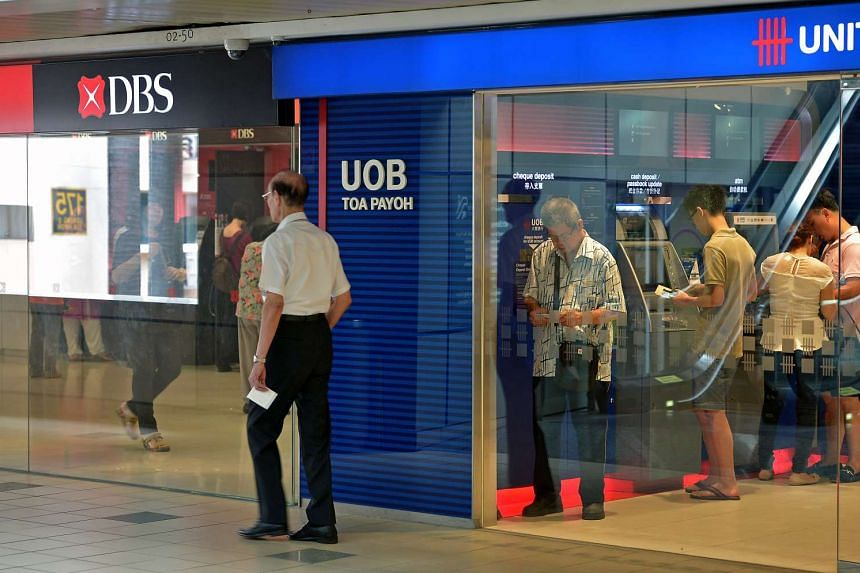 Members of the public using UOB ATM machines located next to DBS bank at Toa Payoh Central.