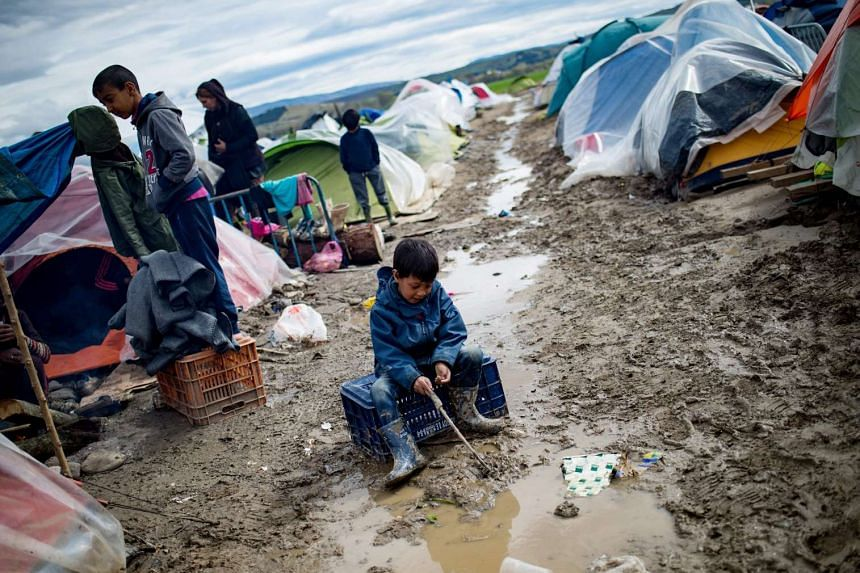 A boy plays in a puddle at a makeshift camp occupied by migrants and refugees at the Greek-Macedonian border near the village of Idomeni on March 24, 2016.