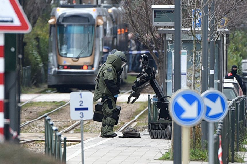 A bomb squad unit agent and a robot stand next to a suspicious object at a tramway station on March 25, 2016, in Schaerbeek suburb, Brussels.