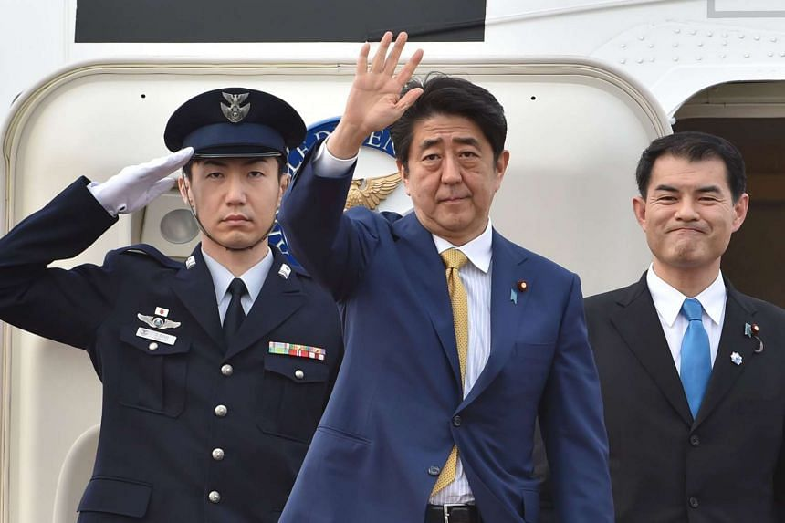 Japan's Prime Minister Shinzo Abe (centre) waves as he departs from Tokyo's Haneda Airport, on March 30, 2016.
