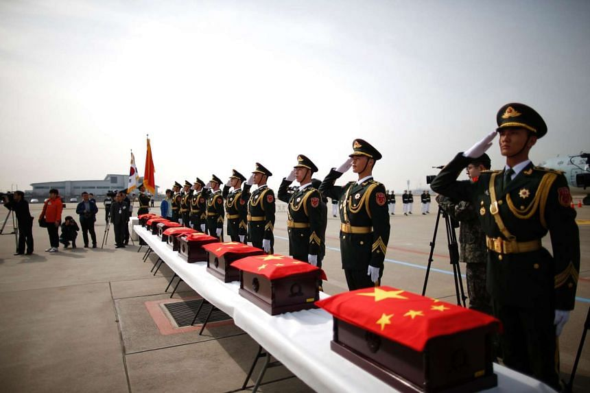 Chinese honour guards salute caskets containing the remains of Chinese soldiers during a handing over ceremony of their remains at the Incheon International Airport, on March 31, 2016.