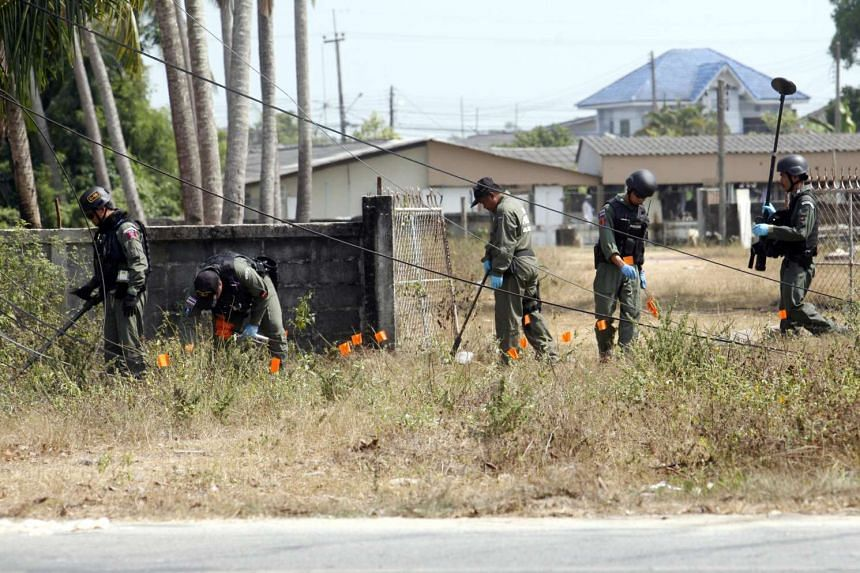 Members of the Explosive Ordnance Disposal (EOD) inspect the area following multiple bomb attacks in Yaring district, Pattani, on March 31, 2016.
