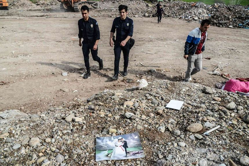Turkish police officers walk past a wedding photograph at a dump on March 30, 2016 in Diyarbakir, the Kurdish-dominated city in southeast Turkey.