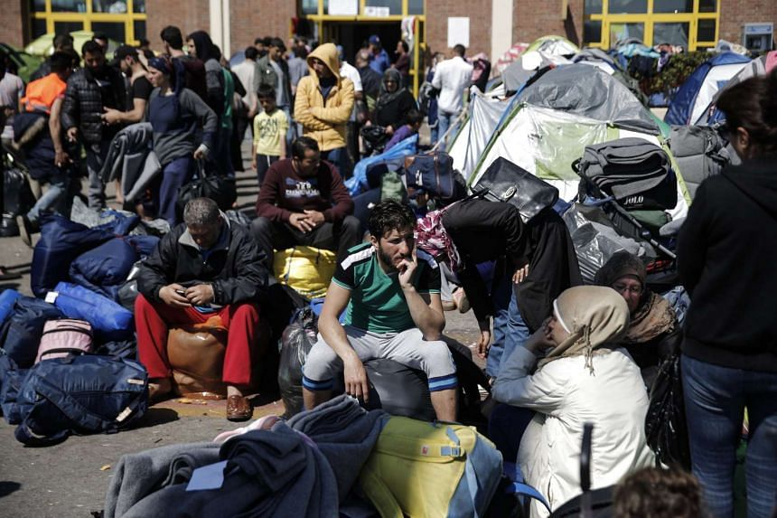 Refugees and migrants sit next to their belongings  at the port of Piraeus, before boarding a bus heading to other parts of the country where they will be accommodated.