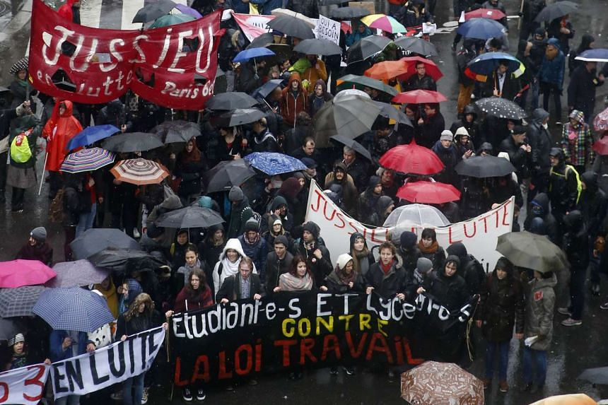 Protesters march with placards during a demonstration against labour law reforms in Paris on March 31, 2016.
