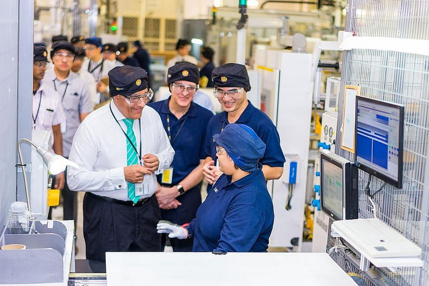 """Mr Iswaran, Minister for Trade and Industry (Industry), speaking to an employee as he toured the REC plant yesterday. He said that REC's investment is a """"strong vote of confidence in the continued attractiveness of Singapore as a manufacturing centre"""