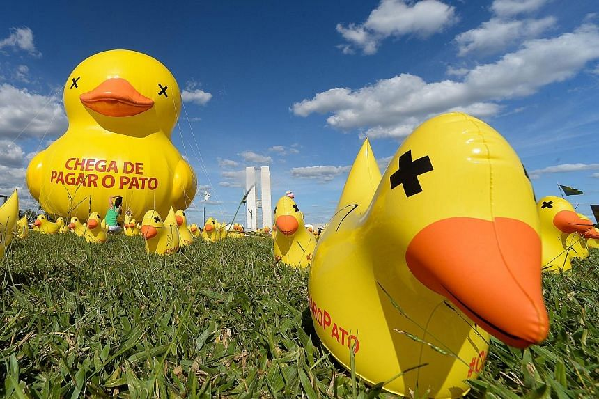 """A Federation of Industries of the State of Sao Paulo protest against taxes at the Esplanada dos Ministerios in Brasilia on Tuesday. The inscription on the giant ducks reads """"Enough of taking the blame""""."""