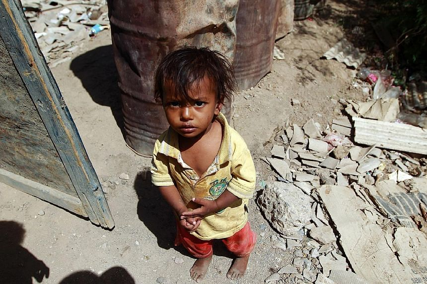 A child outside a house which was destroyed a few months ago in the capital, Sanaa. Unicef says at least six children are killed or maimed every day for the past year.
