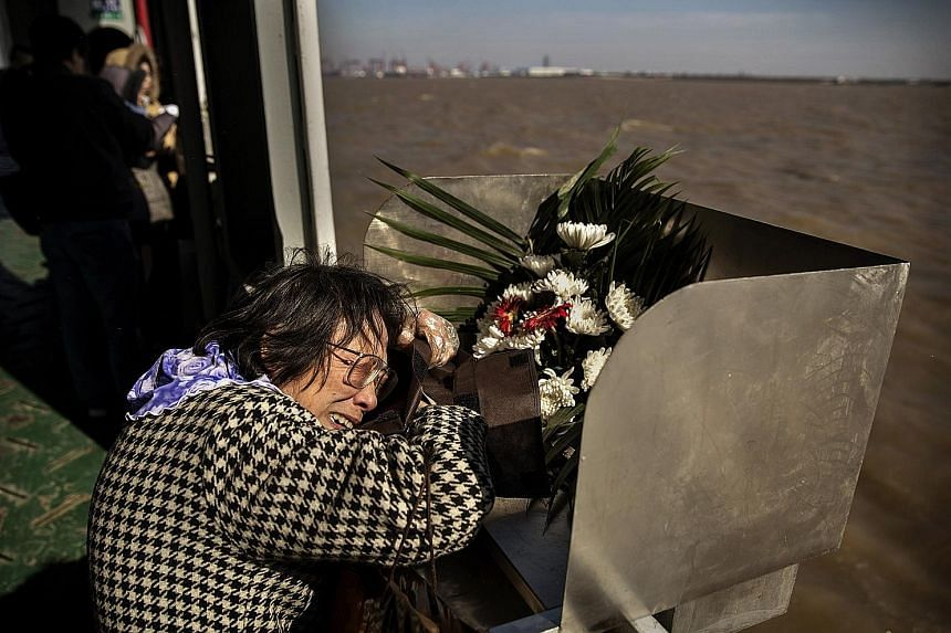 Madam Lin Hui Zhen, 76, clutches the bag carrying the ashes of her late husband Fu Yao Ming, 80, before placing it in a metal chute during a sea burial on a ferry in the East China Sea off Shanghai.