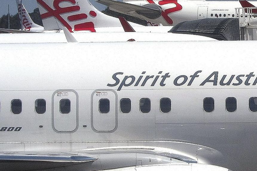 Virgin Australia planes share tarmac space with a Qantas plane. After three consecutive annual losses, Virgin Australia is expected to post a profit in the 12 months ending this June, Bloomberg data shows.