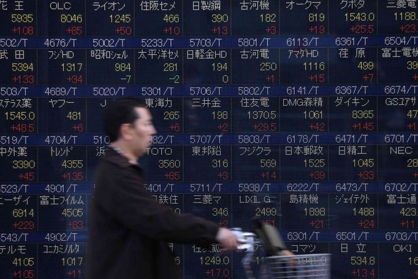 A cyclist goes past a quotation board flashing share prices of the Tokyo Stock Exchange in Tokyo, on March 22, 2016.