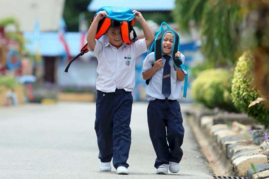 Pupils in Malaysia using their school bags to shelter themselves from the sun.