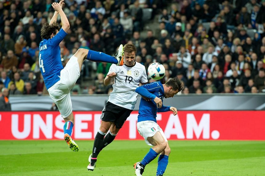 Mario Goetze getting the better of Italy's Matteo Darmian (left) and Alessandro Florenzi to head Germany 2-0 up in Munich. It was the World Cup holders' first win over the Azzurri in 21 years.