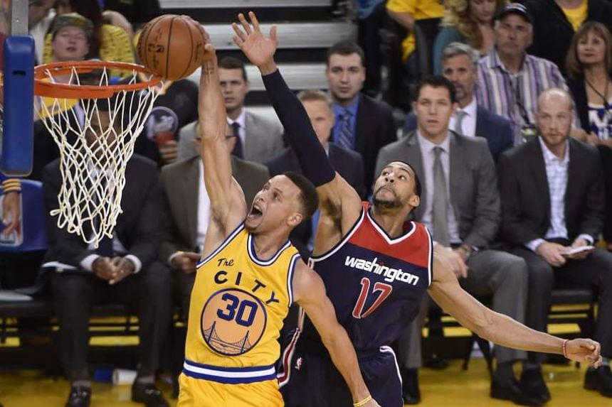 Golden State's Stephen Curry shoots as Washington's Garrett Temple (right) fails to block him during the Warriors' 102-94 win in Oakland. The Warriors need six wins in their final eight games to break Chicago's regular-season record of 72.