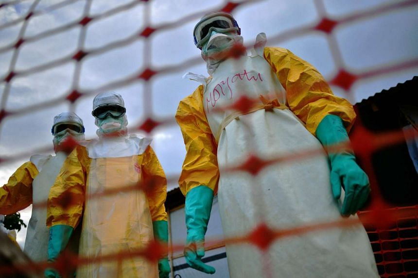 Medical staff wearing protective clothing treating the body of an Ebola victim at their facility in Kailahun, on August 14, 2014.
