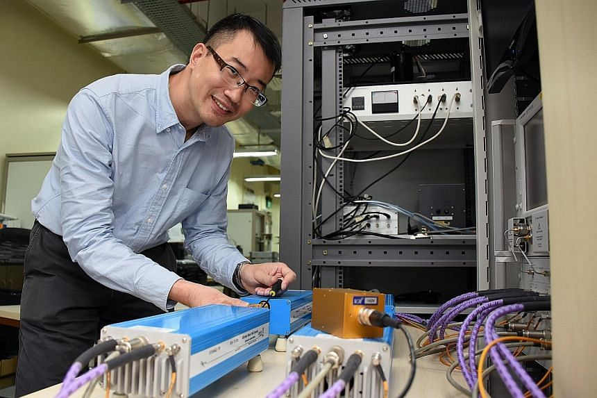 Dr Meng with a network analyser which helps to measure the parameters of radio frequency and microwave components