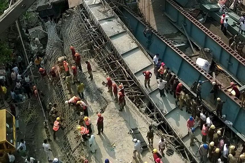 """Rescuers at the site of the accident in Kolkata yesterday. Up to 150 people are believed to be buried under the rubble, and the death toll is expected to rise. Indian media have labelled the disaster """"man-made""""."""