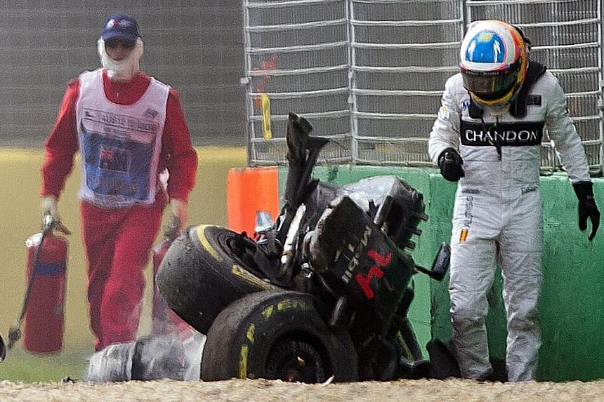 Fernando Alonso (right) walks away from his car after the crash at the Australian Grand Prix in Melbourne on March 20. He will not race in Bahrain after failing a medical test.