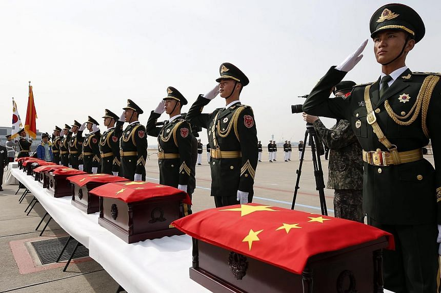 Members of a Chinese honour guard in front of boxes holding the remains of Chinese soldiers killed in the 1950-53 Korean War during a repatriation ceremony yesterday at Incheon Airport in South Korea. The repatriation of the remains of 36 Chinese sol