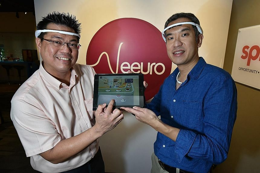 Dr Leong (far left) and Dr Chan wearing the headbands, which measure the brainwaves of users as they play Neeuro Memorie games. On display on the tablet is one of the games, Sushi Recall. It requires players to recreate the sequence in which sushi pl