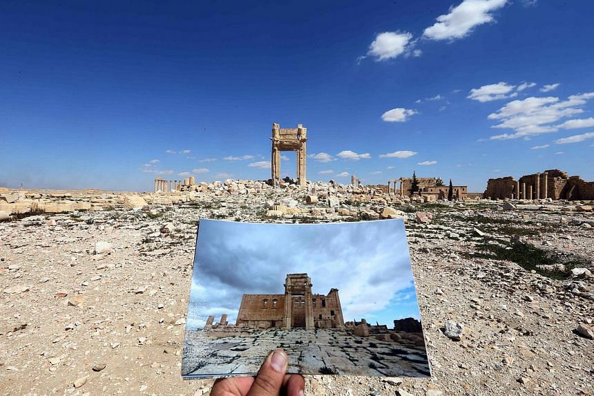 A photographer holding a picture of the Temple of Bel taken on March 14, 2014, in front of the remains of the historic temple in Palmyra.