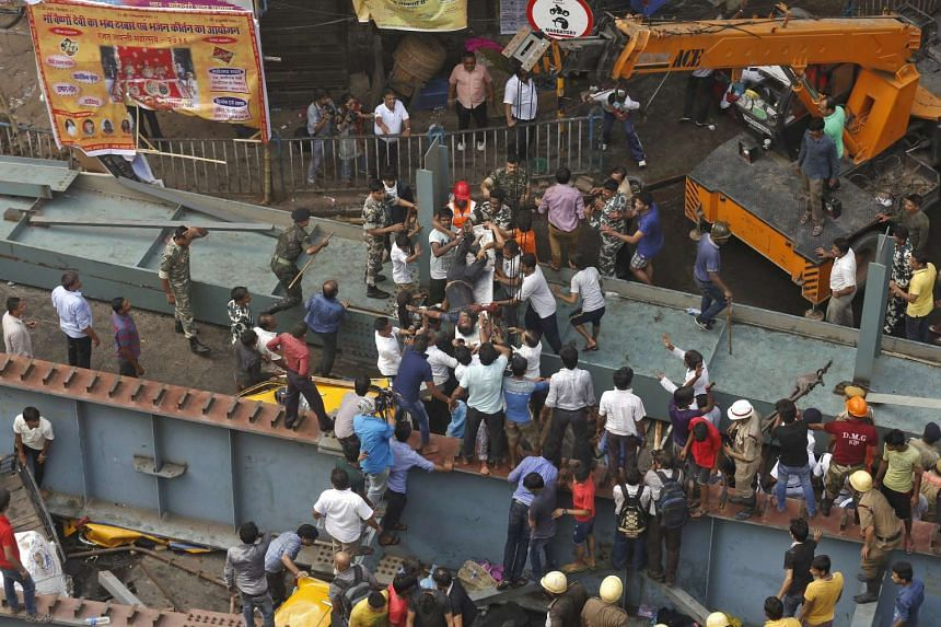 Rescue members carry a victim from the site of an under-construction flyover that collapsed in Kolkata, India, March 31, 2016