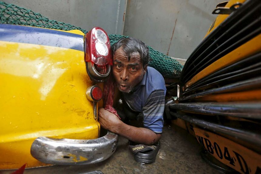 A man is seen trapped amid the debris of an under-construction flyover after it collapsed in Kolkata, India, on March 31, 2016.