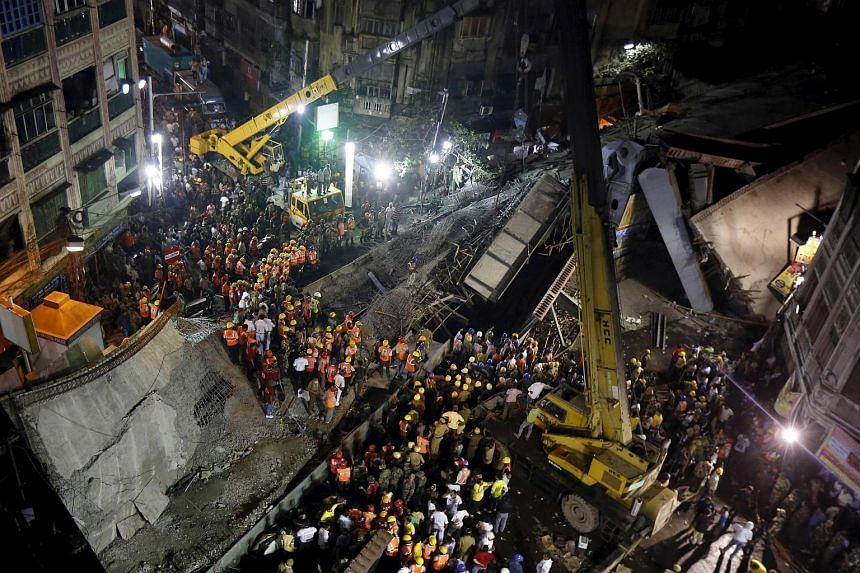 Firefighters and rescue workers search for victims at the site of an under-construction flyover after it collapsed in Kolkata, India, on March 31, 2016.