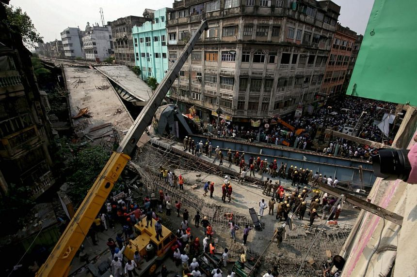 National Disaster Response Force and Indian army personnel work to recover victims after a bridge under construction collapsed in Kolkata, India.