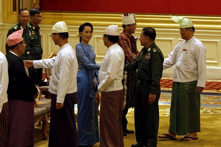 Myanmar's new Foreign Minister Aung San Suu Kyi (centre) shaking hands with military chief Senior General Min Aung Hlaing (second from right) after a handover ceremony at the presidential palace in Naypyitaw, Myanmar, on March 30, 2016.