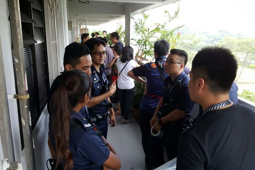 Police officers outside the Ang Mo Kio Avenue 8 flat.