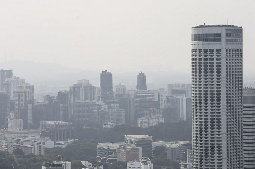 The Swissotel (right) building is pictured against buildings shrouded by haze, on March 30, 2016.