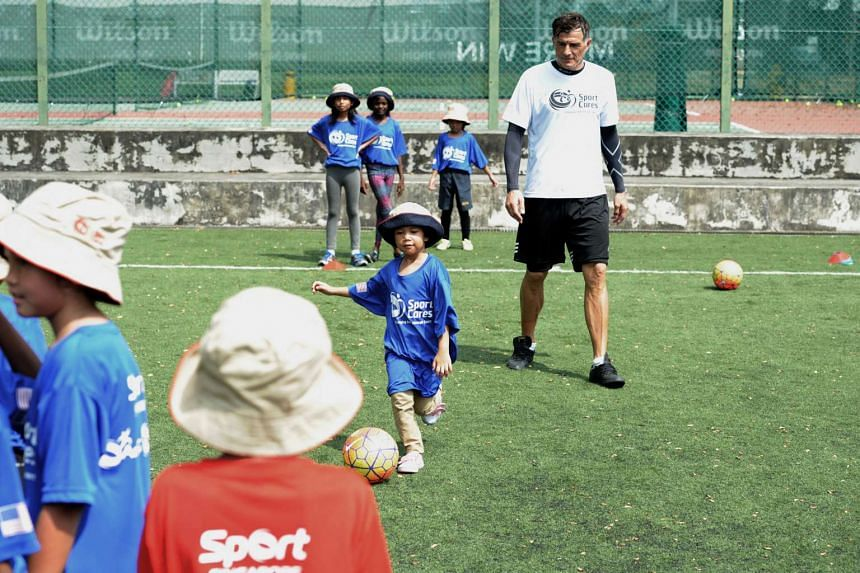 A young participant dribbling under the gaze of ActiveSG Football Academy principal and former national footballer Aleksandar Duric at a football clinic held at St Wilfred Field, on March 17, 2016.