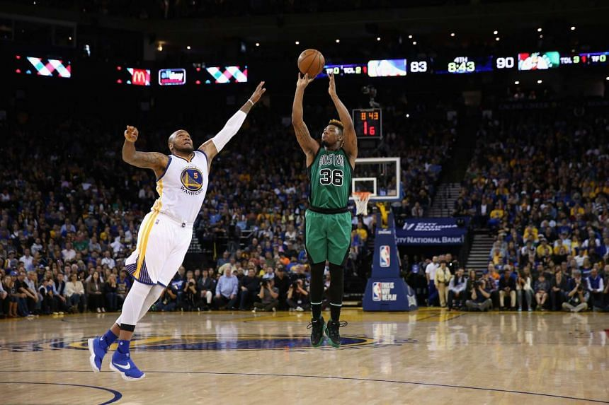 Marcus Smart of the Boston Celtics shoots over Marreese Speights of the Golden State Warriors at ORACLE Arena in Oakland, California.