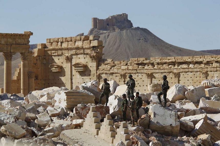 Syrian army soldiers stand on the ruins of the Temple of Bel in Palmyra, Syria.